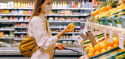 A consumer wearing a face mask buying from a shop during a pandemic